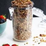 A food storage jar containing maple pecan granola, with two strawberries next to it