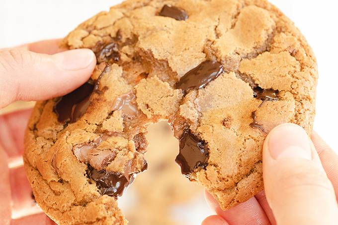 Close up of a chocolate chip cookie being split in half