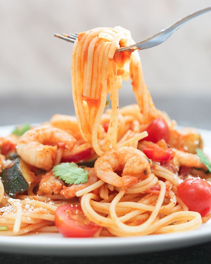 A plate of prawn, chilli and tomato spaghetti with a fork digging in