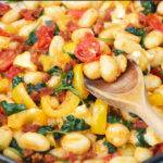Pinterest graphic with text and a photo of cheesy chorizo gnocchi