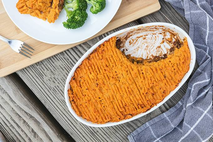Top down view of a large oven dish containing sweet potato cottage pie, with one portion on a white plate next to it