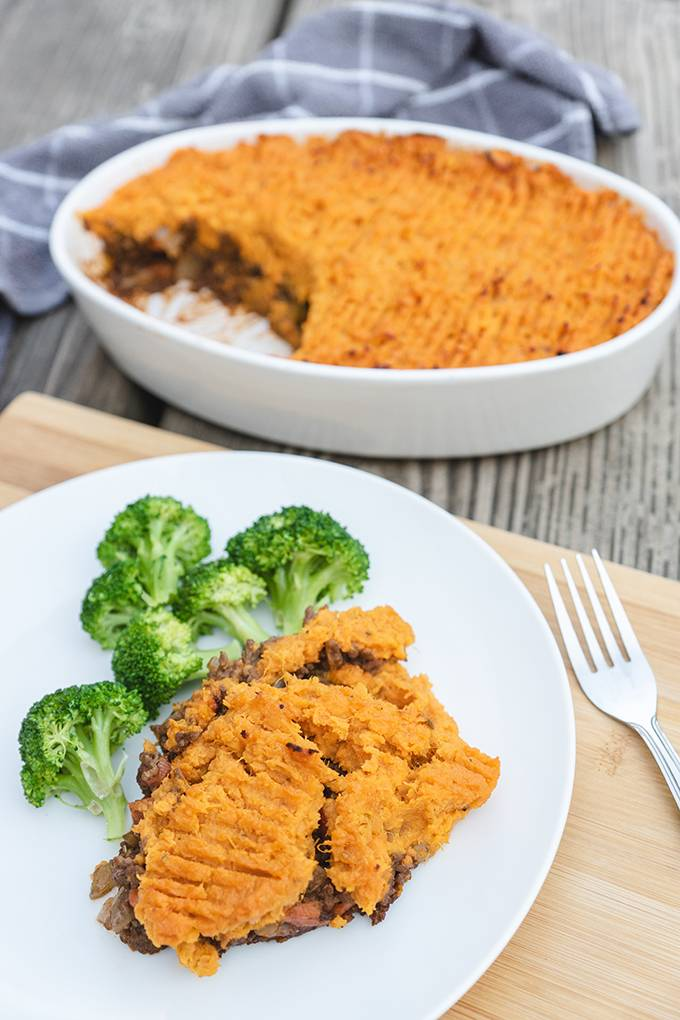 A portion of sweet potato cottage pie on white plate with some broccoli and an oven dish containing the rest of the pie in the background