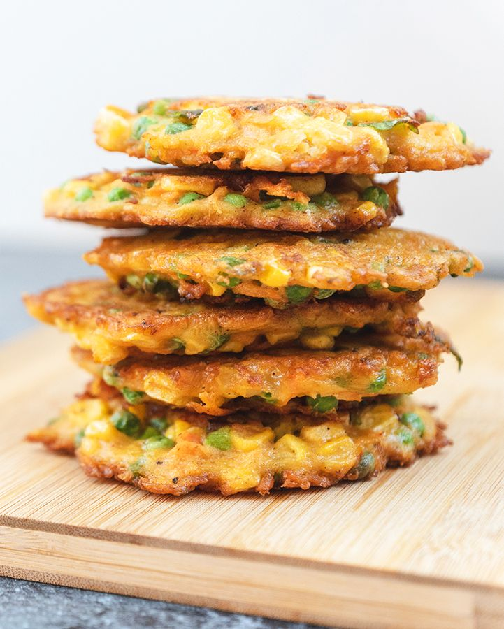 A stack of fried vegetable fritters on a wooden board