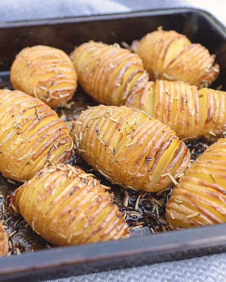 Hasselback potatoes in a black oven tray