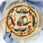 Top down view of a tin of roasted vegetable frittata, with baking paper around the edges.