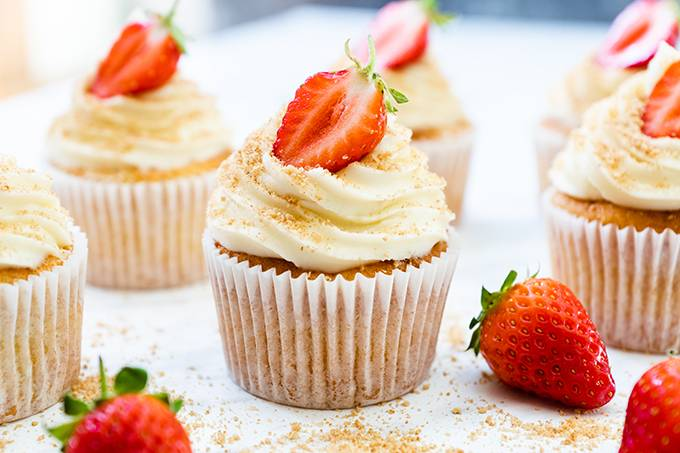 A vanilla cupcake decorated with a white chocolate and cream cheese icing swirl and half a strawberry, surrounded by other cupcakes and strawberries.