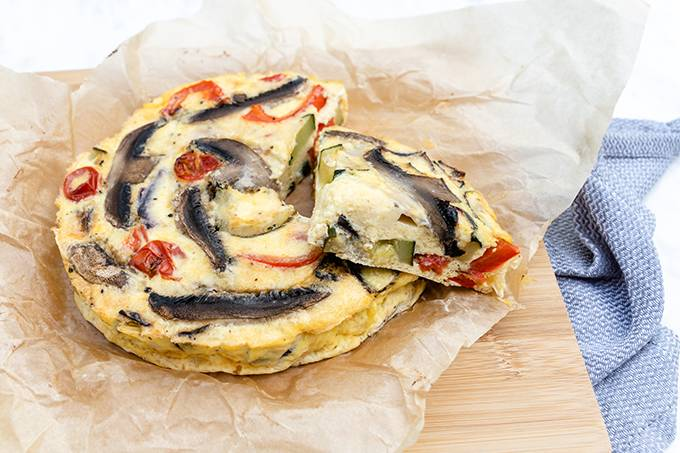 A roasted vegetable frittata on some baking paper on a wooden board, with one slice cut out and resting on top.