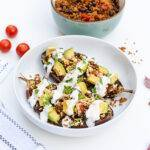A bowl containing two halves of a stuffed aubergine, topped with avocado and yoghurt