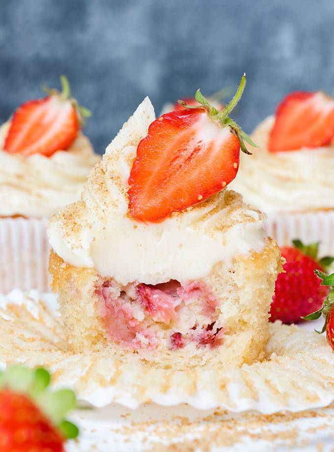 Close up of a white chocolate and strawberry cheesecake cupcake, cut open to reveal baked strawberry pieces in the middle.