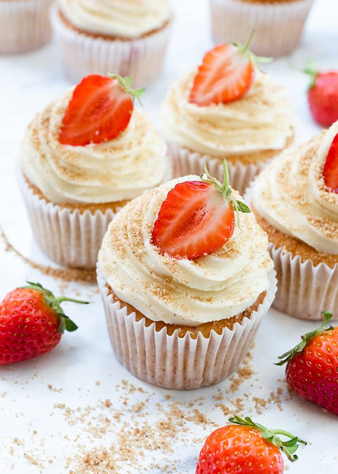 Four cupcakes decorated with white chocolate and cream cheese icing swirls and half a strawberry.