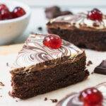 A slice of chocolate biscuit cake with a marbled chocolate topping and a cherry on top.