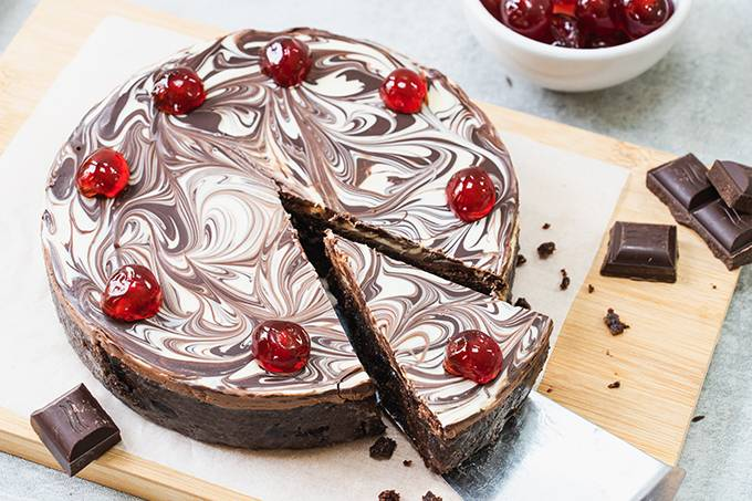 A chocolate biscuit cake with a marbled chocolate topping and cherries on top, with a slice taken out of it.