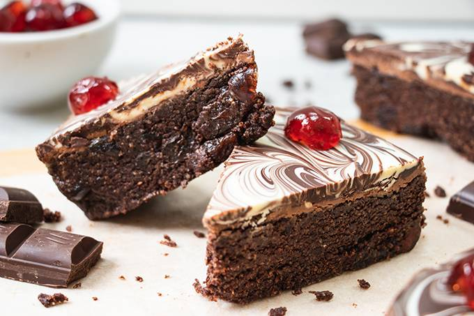 Two slices of chocolate biscuit cake, one propped up against the other. Each has a marbled chocolate topping and a cherry on top.
