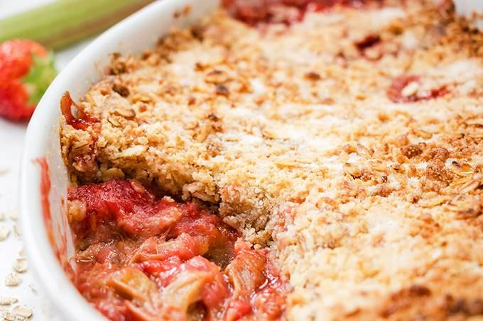 Close up view of a strawberry and rhubarb crumble in a white baking dish