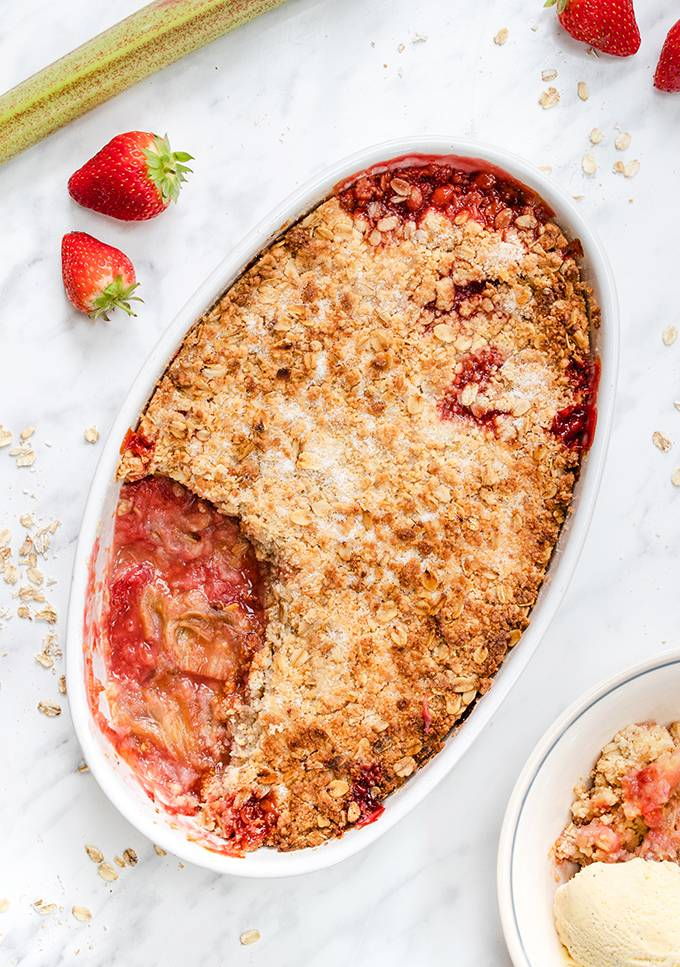Top down view of a strawberry and rhubarb crumble in a white baking dish