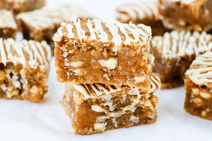 Two peanut butter blondies stacked on top of each other, surrounded by other blondies. Each is drizzled with white chocolate.