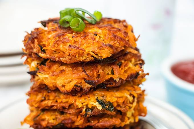 Close up of a stack of crispy sweet potato hash browns with some spring onion slices on top.