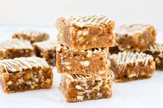 Three peanut butter blondies stacked on top of each other, surrounded by other blondies. Each is drizzled with white chocolate.