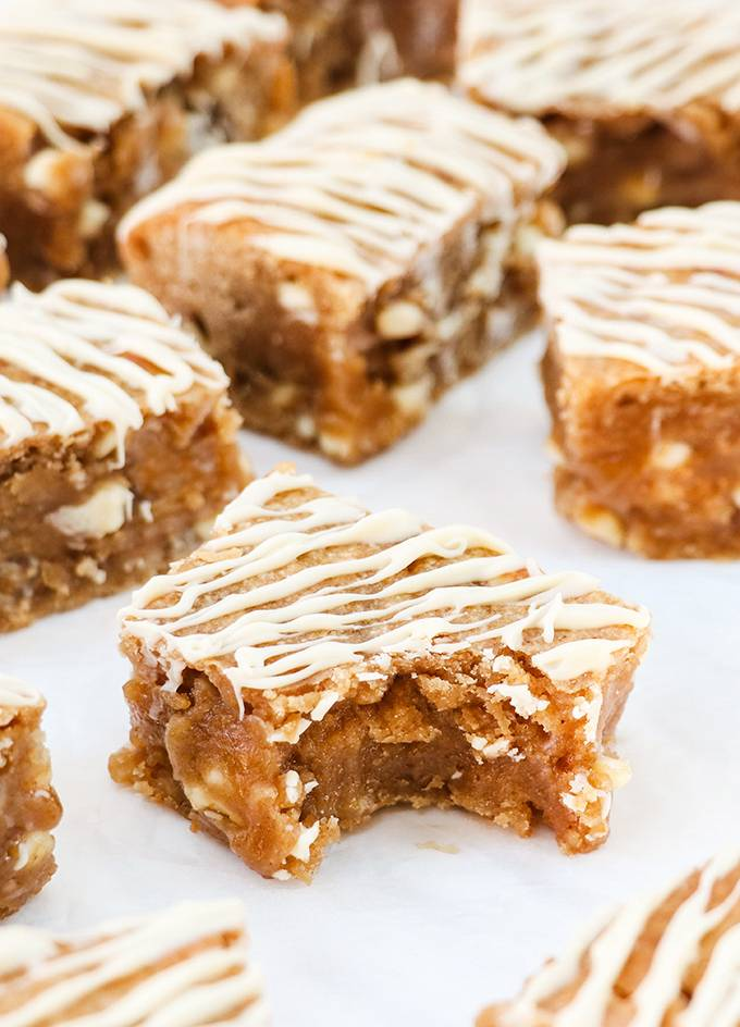Close up of a peanut butter blondie with a bite taken out of it, drizzled in white chocolate and surrounded by other blondies.