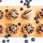Top down view of some gluten free blueberry muffins on a wooden board, surrounded by some clusters of fresh blueberries.
