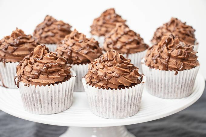 Gluten free nutella filled cupcakes on a white cake stand.