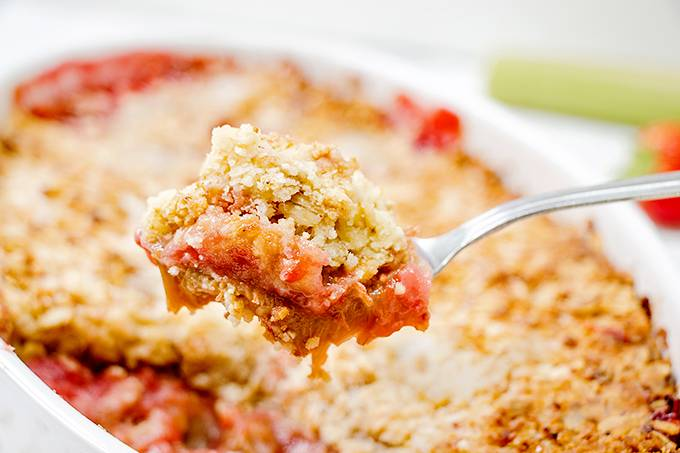 A spoonful of strawberry and rhubarb crumble held over the whole dish of crumble