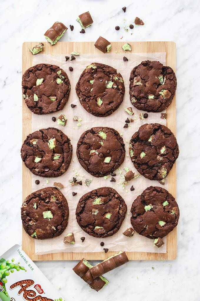 Top down view of a board containing  nine aero mint chocolate chip cookies.