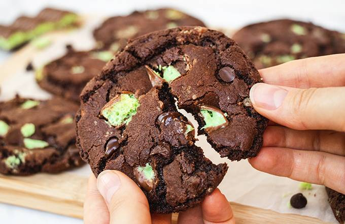 Close up of an aero mint chocolate chip cookie being broken in half.