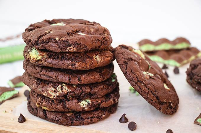 A stack of aero mint chocolate chip cookies with another cookie leaning against it.