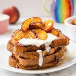 A plate of French toast topped with caramelised peaches and yoghurt