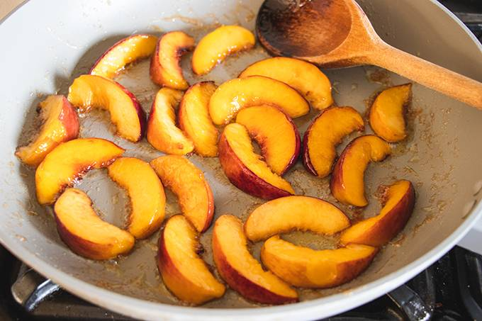 Peach slices caramelising in a saucepan with a wooden spoon resting in it