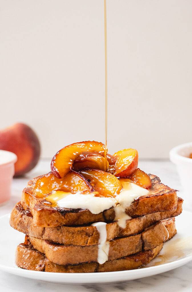 A plate of French toast topped with caramelised peaches and yoghurt, and maple syrup being poured in top
