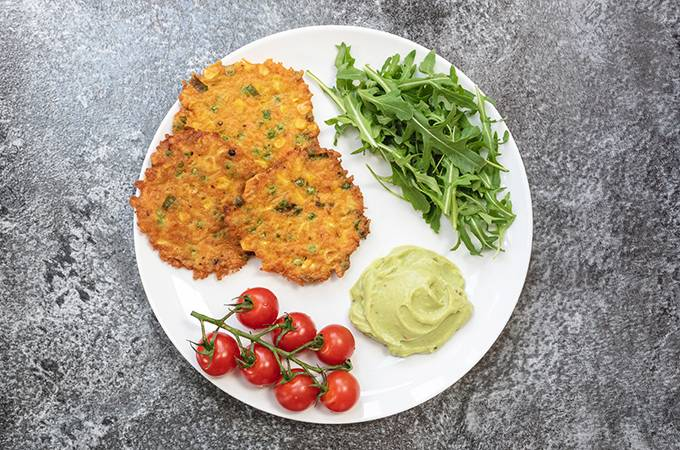 A white plate containing three vegetable fritters, some salad and guacamole.