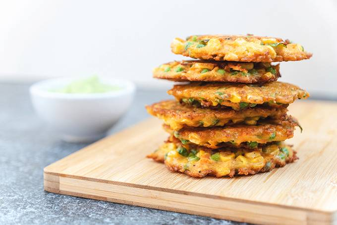 A stack of fried vegetable fritters on a wooden board, next to a white bowl of guacamole