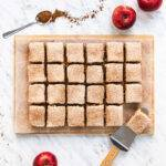 Top down view of 24 squares of apple and cinnamon cake on a wooden board.