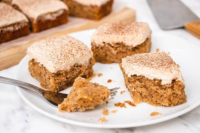 Three squares of apple and cinnamon cake on a white plate, one with a forkful cut away from it.