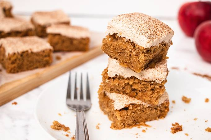 A stack of three squares of apple and cinnamon cake on a white plate with a silver fork next to it.