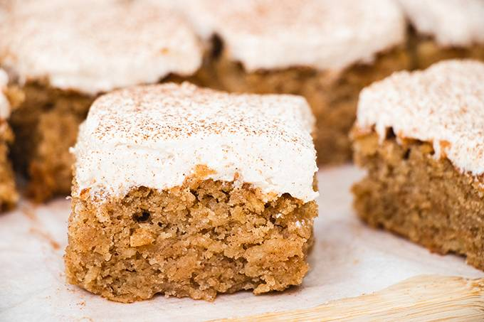 Close up of a square of apple and cinnamon cake with icing on top.