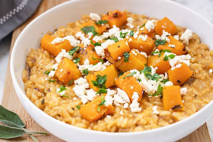 A white bowl containing roasted butternut squash risotto, topped with crumbled feta cheese and fresh sage.