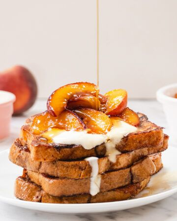 A plate of French toast topped with caramelised peaches and yoghurt, being drizzled with maple syrup