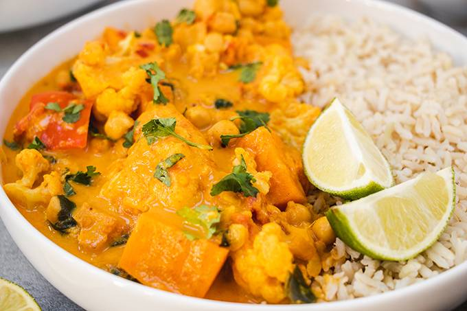 Close up of a bowl of vegetable curry with rice and two wedges of lime