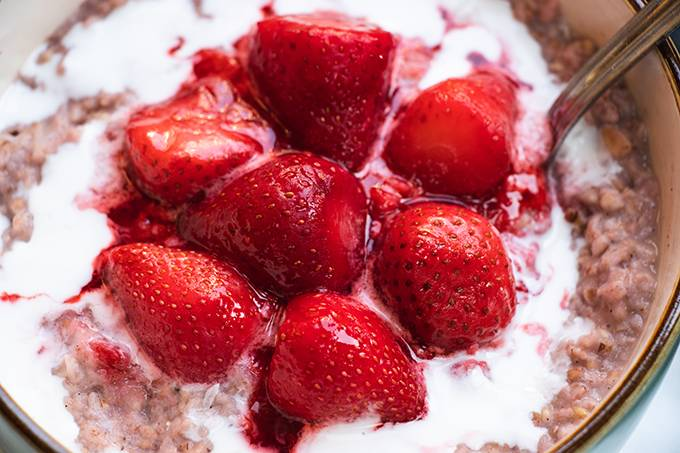 Close up of a bowl of porridge topped with coconut cream and cooked strawberries