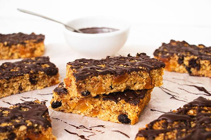 Two chocolate apricot flapjacks stacked, surrounded by other flapjacks and with a pot of melted dark chocolate behind them.