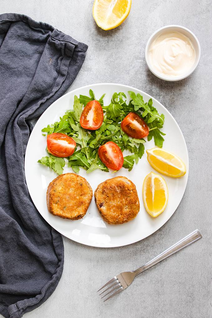 Top down view of a white plate containing two tuna fishcakes, salad and lemon wedges