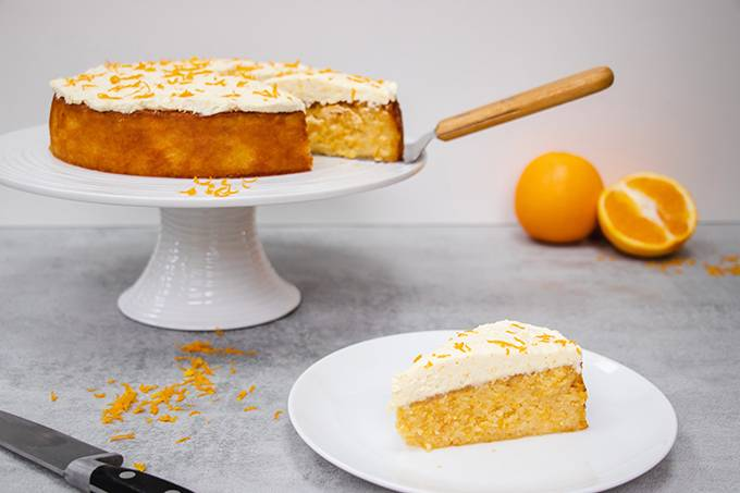 An orange and almond cake on a white cake stand, with one slice separately on a small white plate