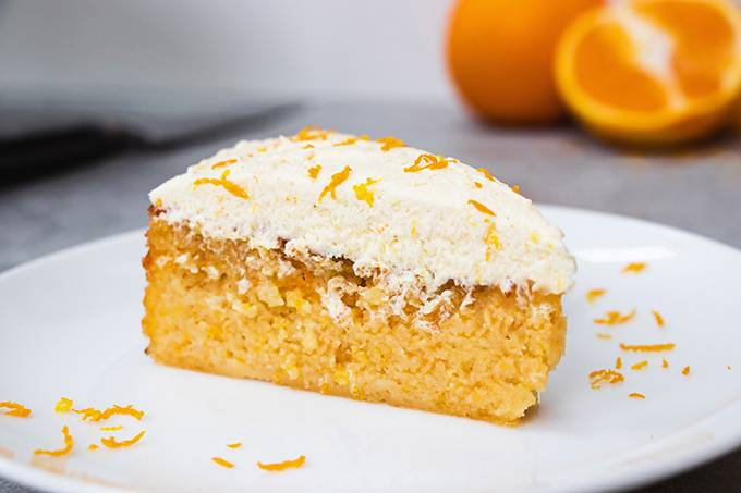 Close up of a slice of orange and almond cake on a white plate, with white buttercream icing and orange zest on top