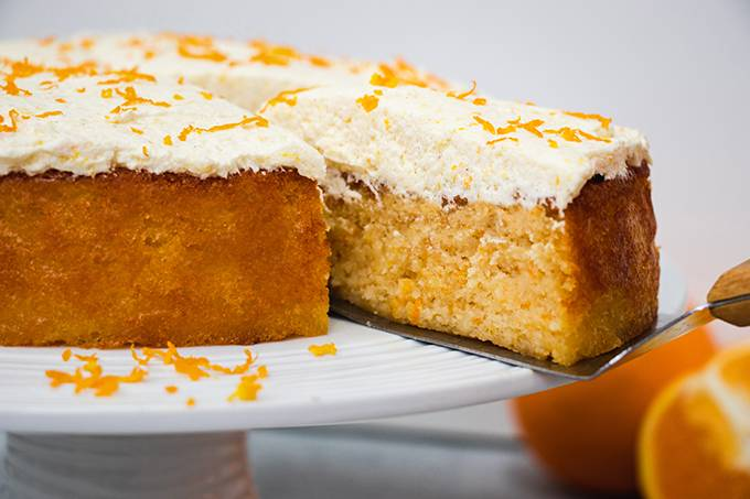 An orange and almond cake on a white cake stand with a slice being taken out of it