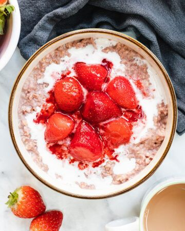 Top down view of a bowl of porridge topped with coconut cream and cooked strawberries