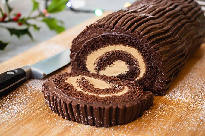 Close up of a Christmas chocolate yule log, with one slice cut off the end