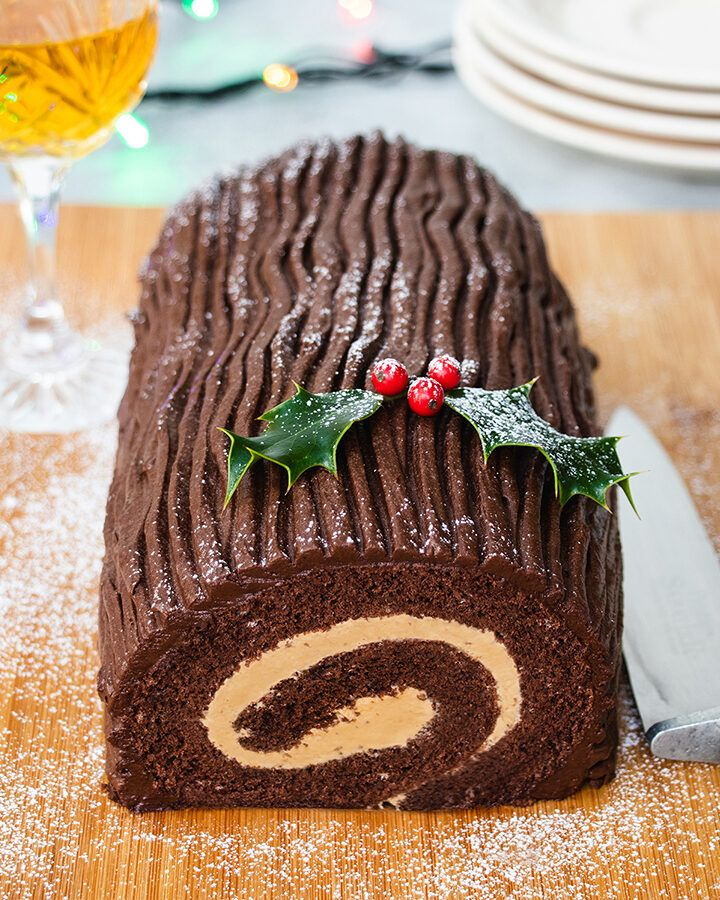 A Christmas chocolate yule log on a wooden board, decorated with a piece of holly